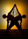 Yoga de pratique de deux personnes dans la lumière de coucher du soleil Image libre de droits