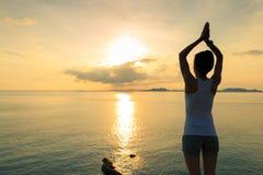 Yoga de pratique de femme au bord de la mer de lever de soleil Images stock