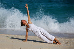 Yoga de pratique de femme caucasienne au bord de la mer Photographie stock