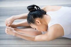 Yoga de pratique de femme dans la pose de recourbement en avant Photo libre de droits