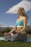 Yoga de pratique de femme dans Lotus Position Image stock