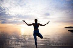 Yoga de pratique de femme de silhouette sur la plage de coucher du soleil Images libres de droits