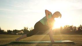Yoga de pratique de femme en bonne santé adulte au coucher du soleil banque de vidéos