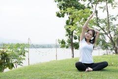 yoga de pratique de femme enceinte d'Asiatique tout en écoutant la musique dessus Photos stock