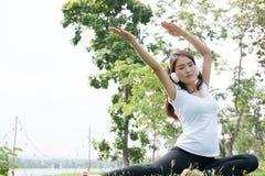 yoga de pratique de femme enceinte d'Asiatique tout en écoutant la musique dessus Images stock