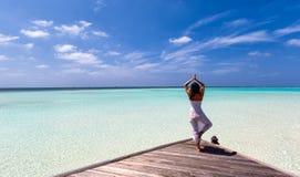 Yoga de pratique de femme sur une jetée Images stock