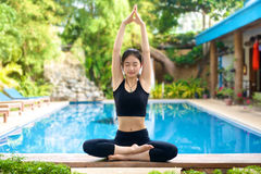 Yoga de pratique de fille asiatique sur un banc Photographie stock libre de droits