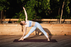Yoga de pratique de jeune belle fille blonde dehors au lever de soleil Image libre de droits