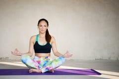 Yoga de pratique de jeune femme à un arrière-plan urbain Photos stock