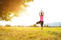 Yoga de pratique de jeune femme sportive sur un pré au coucher du soleil photographie stock
