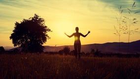 Yoga de pratique de jeune femme sportive sur un pré au coucher du soleil images stock