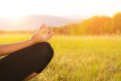 Yoga de pratique de jeune femme sportive sur un pré au coucher du soleil photos libres de droits