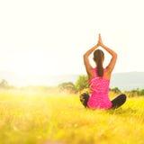 Yoga de pratique de jeune femme sportive sur un pré au coucher du soleil images libres de droits
