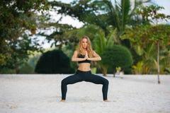 Yoga de pratique de jeune femme sur la plage Image stock