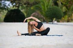 Yoga de pratique de jeune femme sur la plage Photos libres de droits