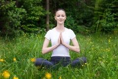 Yoga de pratique de jeune fille dans une forêt Photos stock