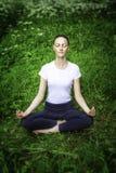 Yoga de pratique de jeune fille dans une forêt Photographie stock