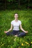 Yoga de pratique de jeune fille dans une forêt Images stock