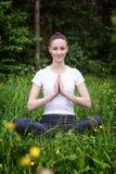 Yoga de pratique de jeune fille dans une forêt Image stock