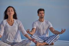 Yoga de pratique de jeunes couples Photos libres de droits