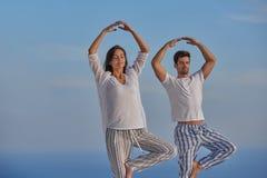 Yoga de pratique de jeunes couples Image stock