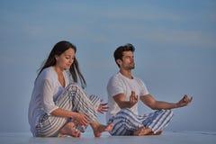 Yoga de pratique de jeunes couples Photos stock