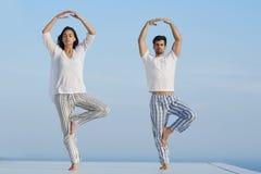 Yoga de pratique de jeunes couples Photographie stock libre de droits