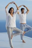 Yoga de pratique de jeunes couples Photo stock