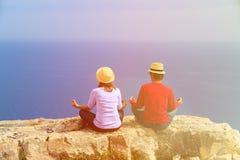 Yoga de pratique de jeunes couples en montagnes scéniques Photographie stock