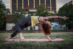 Yoga de pratique de jolie jeune femme en parc (courbure arrière) images stock