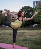 Yoga de pratique de jolie jeune femme en parc (danseur Pose) photographie stock libre de droits