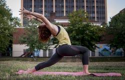 Yoga de pratique de jolie jeune femme en parc (guerrier) photos libres de droits