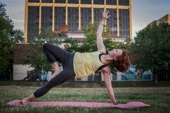 Yoga de pratique de jolie jeune femme en parc (planche latérale) image libre de droits