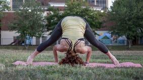 Yoga de pratique de jolie jeune femme en parc (trépied) photos libres de droits
