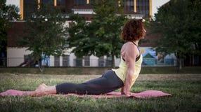 Yoga de pratique de jolie jeune femme en parc (vers le haut du chien) image stock