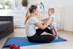 Yoga de pratique de sourire de mère sur le tapis de forme physique au salon Image stock