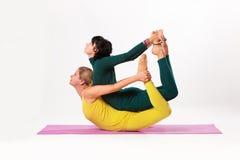Yoga de pratique en matière de femme supérieure et plus jeune Images stock