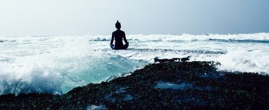 Yoga de pratique en matière de femme au bord de la mer photos libres de droits