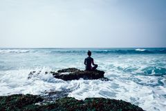 Yoga de pratique en matière de femme au bord de la mer photo libre de droits