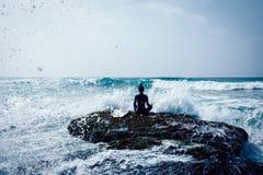 Yoga de pratique en matière de femme au bord de la mer image libre de droits