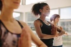 Yoga de pratique en matière de femme avec des amis dans le gymnase Photographie stock