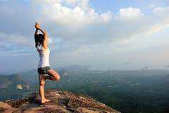 Yoga de pratique en matière de femme au bord de la mer de lever de soleil Photographie stock libre de droits