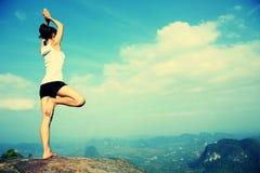 Yoga de pratique en matière de femme au bord de la mer de lever de soleil Photos stock