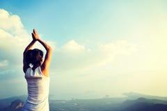 Yoga de pratique en matière de femme au bord de la mer de lever de soleil Images libres de droits