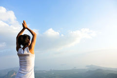Yoga de pratique en matière de femme au bord de la mer de lever de soleil Image libre de droits