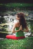Yoga de pratique en matière de jeune femme extérieur Image stock