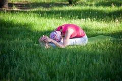 Yoga de pratique et gymnastique de jeune femme flexible en parc Yoga en parc, dehors, santé du ` s de femmes, femme de yoga Image stock