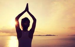 Yoga de pratique de femme à la côte de lever de soleil Photos libres de droits