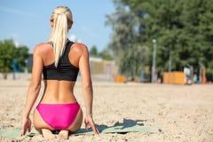 Yoga de pratique de femme blonde bronzé par Caucasien à la plage L'espace pour le texte photographie stock