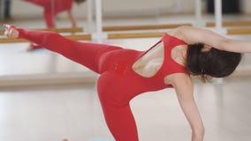 Yoga de pratique de femme dans un studio ? l'int?rieur Yoga faisant femelle dans un studio avec la lumi?re naturelle banque de vidéos